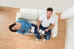 Jeunes couples de sourire tenant le comprimé numérique Photos libres de droits