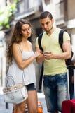 Jeunes couples de sourire trouvant le chemin avec le téléphone Photo libre de droits