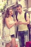 Jeunes couples de sourire trouvant le chemin avec le téléphone Images stock