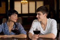 Jeunes couples de sourire une date buvant  Photographie stock libre de droits