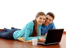 Jeunes couples de sourire utilisant l'ordinateur portatif à la maison Image stock