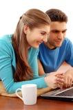 Jeunes couples de sourire utilisant l'ordinateur portatif à la maison Photo libre de droits