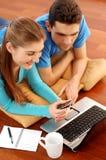 Jeunes couples de sourire utilisant l'ordinateur portatif à la maison Image libre de droits