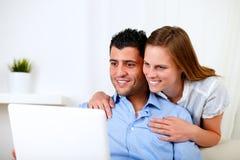 Jeunes couples de sourire utilisant l'ordinateur portatif Images libres de droits