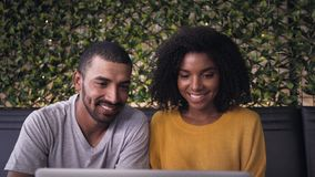Jeunes couples de sourire utilisant l'ordinateur portatif banque de vidéos