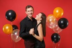 Jeunes couples de stupéfaction dans des vêtements noirs célébrant la fête de vacances d'anniversaire d'isolement sur les ballons  photographie stock libre de droits