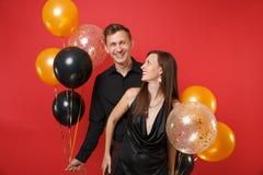Jeunes couples de stupéfaction dans des vêtements noirs célébrant la fête de vacances d'anniversaire sur les ballons à air rouges images stock