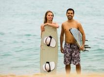 Jeunes couples de surfers sur la plage Photo stock
