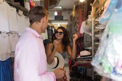 Jeunes couples de touriste choisissant des lunettes de soleil sur de nouveaux verres de Sun de marché en plein air de Chherful d' Photos libres de droits