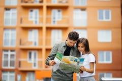 Jeunes couples de touristes voyageant sur le sourire de vacances dehors heureux Famille caucasienne avec la carte de ville à la r Photo stock