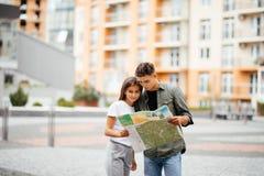 Jeunes couples de touristes voyageant sur le sourire de vacances dehors heureux Famille caucasienne avec la carte de ville à la r Photo libre de droits