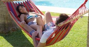 Jeunes couples de vacances détendant dans un hamac Photographie stock