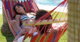 Jeunes couples de vacances détendant dans un hamac Images libres de droits