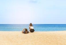 Jeunes couples de vue arrière détendant sur la plage tropicale Photos stock