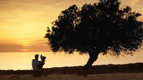 Jeunes couples des amants dans le coucher du soleil sur le fond de l'océan photographie stock