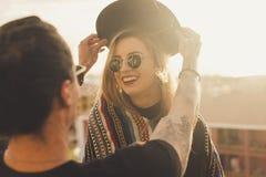 Jeunes couples des amis ayant l'amusement sur la terrasse pendant le coucher du soleil Images stock