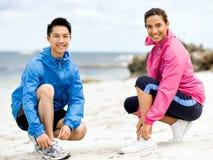 Jeunes couples des coureurs attachant la dentelle au bord de la mer Photos libres de droits
