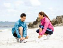 Jeunes couples des coureurs attachant la dentelle au bord de la mer Images stock