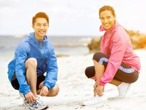 Jeunes couples des coureurs attachant la dentelle au bord de la mer Photos stock