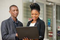 Jeunes couples des hommes d'affaires avec un ordinateur portable photographie stock libre de droits