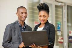 Jeunes couples des hommes d'affaires avec un ordinateur portable photos libres de droits