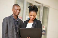 Jeunes couples des hommes d'affaires avec un ordinateur portable image libre de droits