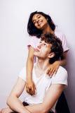 Jeunes couples des métis amie et ami ayant l'amusement sur le fond blanc, concept adolescent de personnes de mode de vie Image stock