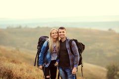 Jeunes couples des touristes avec des sacs à dos sur la nature Photos libres de droits