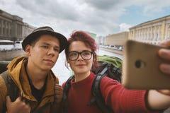 Jeunes couples des touristes prenant des selfies dans la perspective de l'architecture Image stock