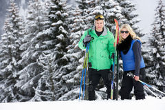 Jeunes couples des vacances de ski en montagnes Image libre de droits