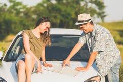 Jeunes couples des voyageurs regardant la carte de touristes dehors concept de course Photo libre de droits