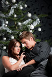 Jeunes couples devant l'arbre de Noël Image stock