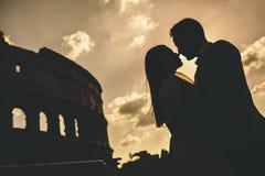 Jeunes couples devant le Colosseum à Rome au coucher du soleil Photo stock