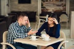 Jeunes couples discutant dans un café Elle le ` s a eu assez, ami fait des excuses Problèmes de relations Photographie stock