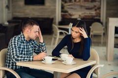 Jeunes couples discutant dans un café Elle le ` s a eu assez, ami fait des excuses Problèmes de relations Photos stock