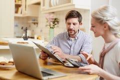 Jeunes couples discutant des finances à la cuisine image libre de droits