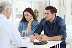 Jeunes couples discutant le plan de retraite de retraite avec le conseiller dans le bureau Photo stock