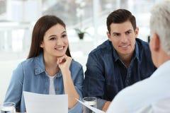 Jeunes couples discutant le plan de retraite de retraite avec le conseiller dans le bureau Photos libres de droits