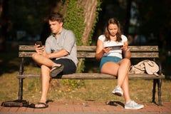 Jeunes couples distraits avec le comprimé de technologie des communications et Photographie stock