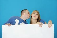 Jeunes couples doux embrassant derrière la couverture blanche Images stock