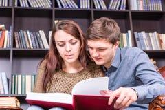 Jeunes couples doux lisant un livre à la bibliothèque Photos libres de droits