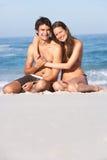 Jeunes couples détendant sur les vêtements de bain s'usants de plage Images stock