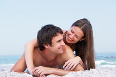 Jeunes couples détendant sur les vêtements de bain s'usants de plage Images libres de droits