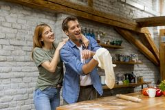 Jeunes couples durcissant la pizza dans la cuisine ensemble image stock