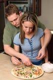 Jeunes couples effectuant la pizza Photos stock