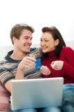 Jeunes couples effectuant les achats en ligne Photographie stock
