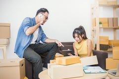 Jeunes couples emballant et déplaçant leur maison, emballage de marketing en ligne et livraison, Photographie stock