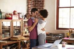 Jeunes couples embrassant dans la cuisine, longueur de trois-quarts Image stock