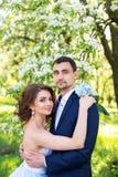 Jeunes couples embrassant dans le jardin de floraison de ressort Amour et thème romantique Photos stock