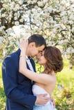 Jeunes couples embrassant dans le jardin de floraison de ressort Amour et thème romantique Photographie stock